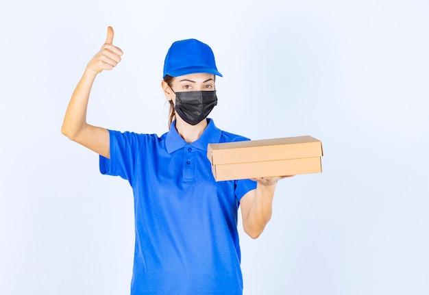 Weiblicher kurier in blauer uniform und gesichtsmaske, der einen karton hält und ein freudenhandzeichen zeigt.