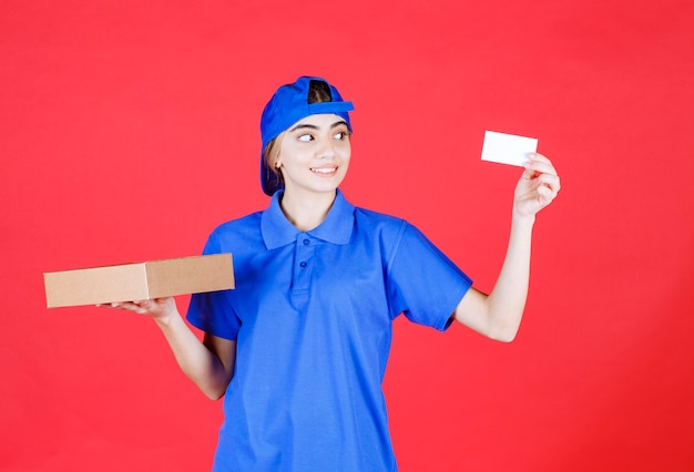 Weiblicher kurier in der blauen uniform, die eine mitnahmebox hält und ihre visitenkarte präsentiert.