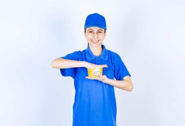 Weiblicher kurier in der blauen uniform, die eine nudelbecher zum mitnehmen hält.