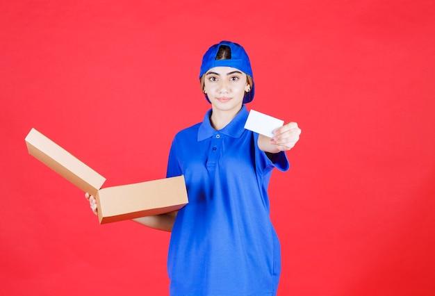 Weiblicher kurier in der blauen uniform, die eine pappschachtel zum mitnehmen hält und ihre visitenkarte präsentiert.