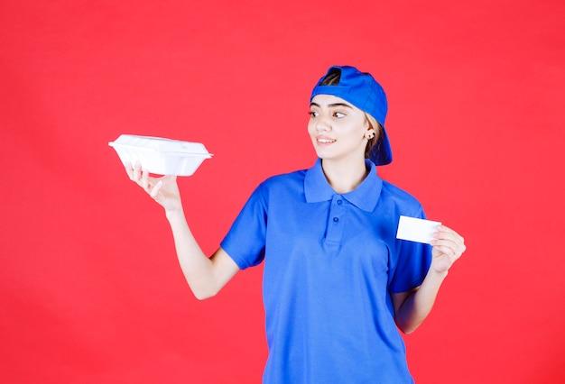 Weiblicher kurier in der blauen uniform, die eine weiße imbissbox hält und ihre visitenkarte präsentiert.