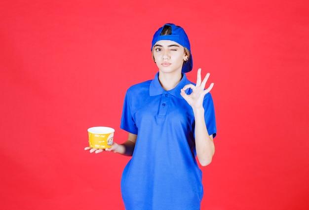 Weiblicher kurier in der blauen uniform, die einen gelben nudelbecher hält und zufriedenheitszeichen zeigt.