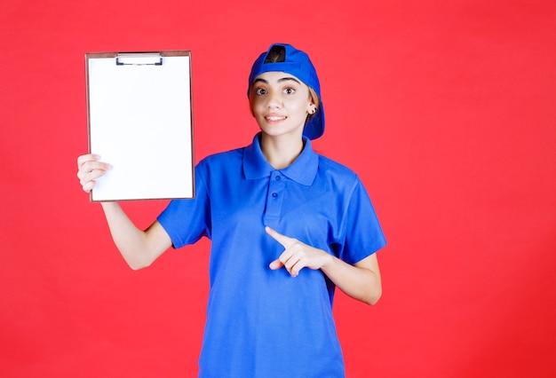 Weiblicher kurier in der blauen uniform, die einen kunden leer hält.