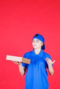 Weiblicher kurier in der blauen uniform, die einen pappkarton hält.