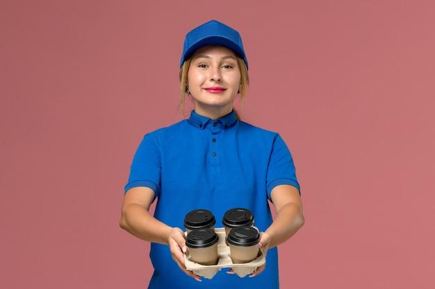 Weiblicher kurier in der blauen uniform, die lieferbecher des kaffees mit lächeln auf rosa, dienstarbeiter-jobuniformlieferung hält