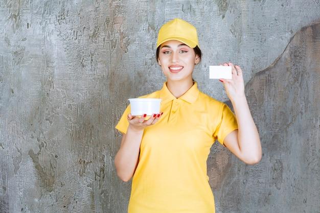 Weiblicher kurier in der gelben uniform, die eine tasse zum mitnehmen hält und ihre visitenkarte präsentiert.