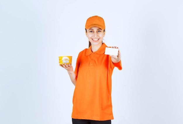 Weiblicher kurier in der gelben uniform, die einen nudelbecher zum mitnehmen hält und ihre visitenkarte präsentiert.