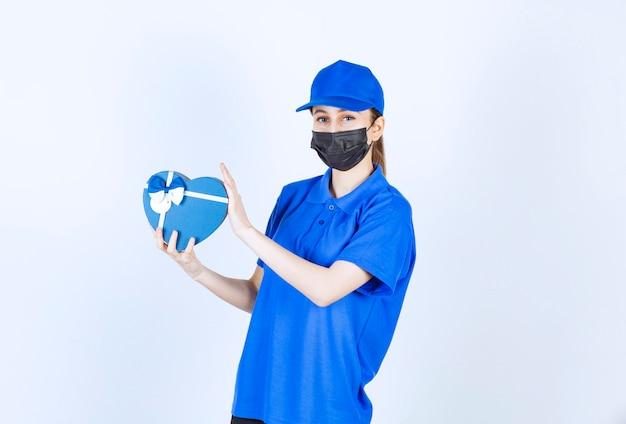 Weiblicher kurier in der maske und in der blauen uniform, die eine herzform-geschenkbox halten.