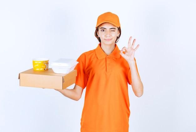 Weiblicher kurier in der orange uniform, die gelbe und weiße imbissboxen hält