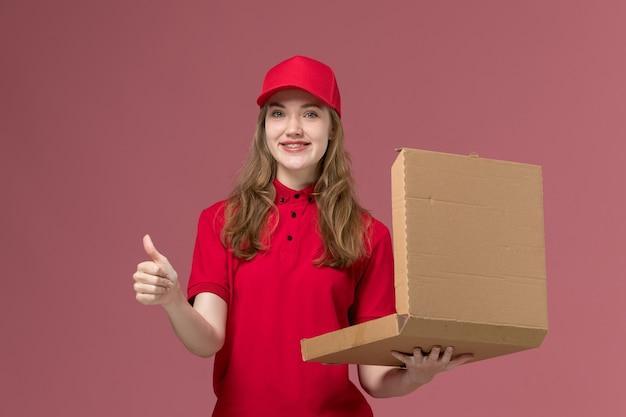 Weiblicher kurier in der roten uniform, die lebensmittel-lieferbox auf rosa, einheitlichem service-lieferarbeiter hält