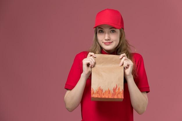 Weiblicher kurier in der roten uniform, die lebensmittelpaket hält, das auf rosa, einheitlichem dienstlieferungsjobarbeiter aufwirft