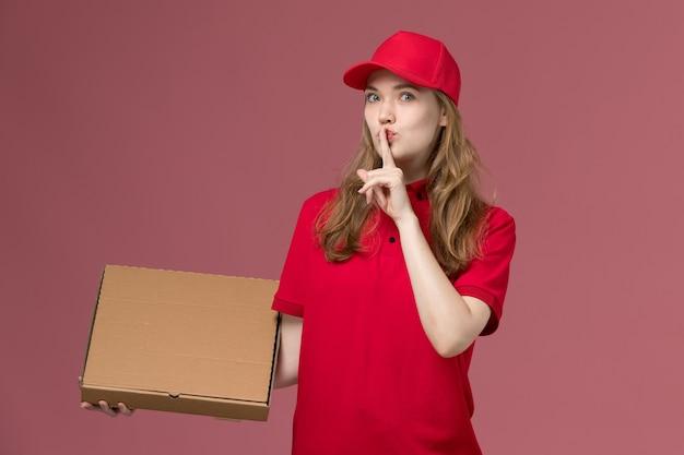 Weiblicher kurier in der roten uniform, die nahrungsmittelbox hält, die schweigenzeichen auf hellrosa, arbeitsuniform-dienstarbeiterlieferung zeigt