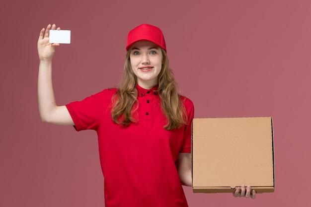 Weiblicher kurier in der roten uniform, die weiße karte und nahrungsmittelbox auf rosa, einheitlicher dienstlieferungsarbeitsjob hält