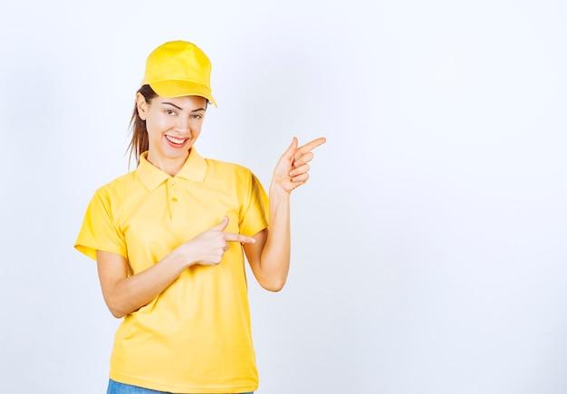 Weiblicher kurier in gelber uniform, der auf irgendwo zeigt.