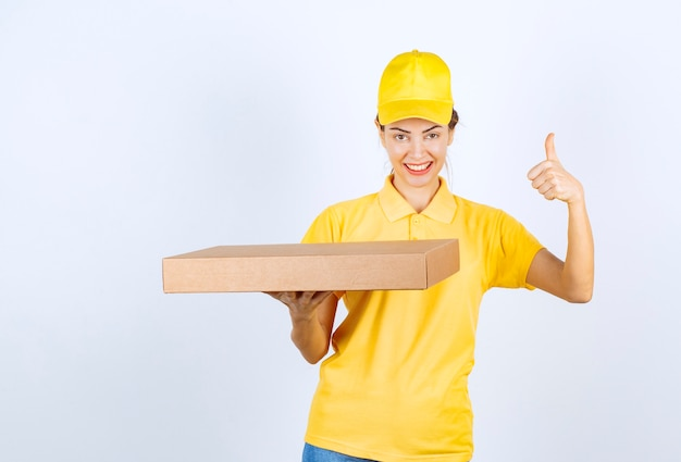 Weiblicher kurier in gelber uniform, der ein papppaket hält und freudenhandzeichen zeigt.