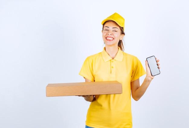Weiblicher kurier in gelber uniform, der ein papppaket hält und ihr weißes smartphone zeigt.