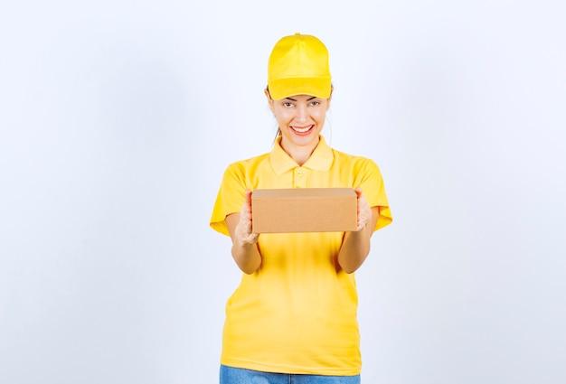Weiblicher kurier in gelber uniform, der ein papppaket liefert und sich positiv fühlt.