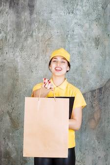 Weiblicher kurier in gelber uniform, der eine einkaufstasche aus pappe liefert und einen schwarzen ordner hält.