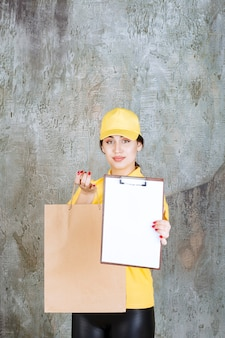 Weiblicher kurier in gelber uniform, der eine einkaufstüte aus karton liefert und den rohling zur unterschrift vorlegt.