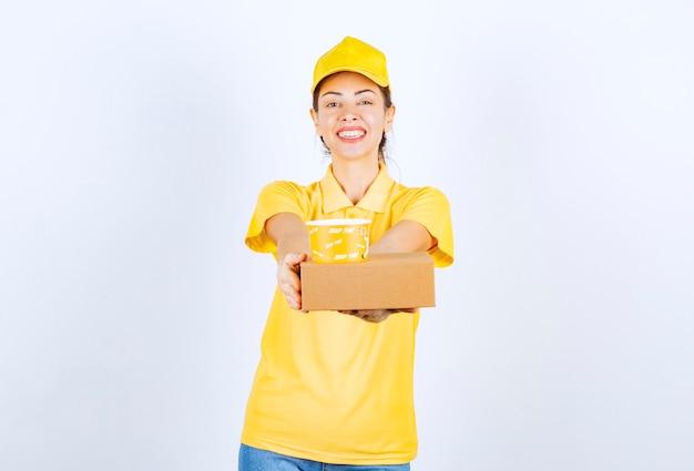 Weiblicher kurier in gelber uniform, der eine lieferung zum mitnehmen durchführt.
