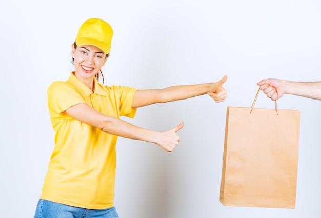 Weiblicher kurier in gelber uniform, der eine pappeinkaufsbox erhält und daumen nach oben zeigt.