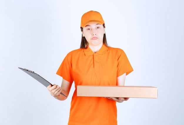 Weiblicher kurier in gelber uniform, der eine pappschachtel zum mitnehmen hält und die adressliste überprüft und verwirrt aussieht.