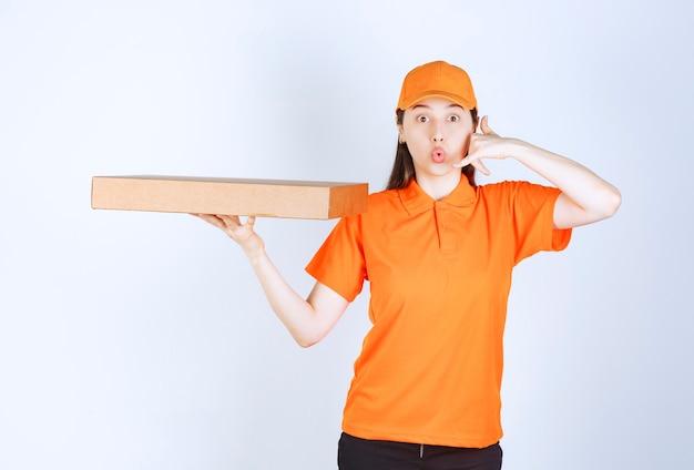 Weiblicher kurier in gelber uniform, der eine pappschachtel zum mitnehmen hält und um einen anruf bittet.