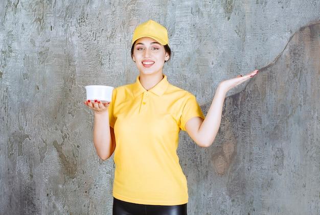 Weiblicher kurier in gelber uniform, der eine tasse zum mitnehmen hält und auf jemanden zeigt.