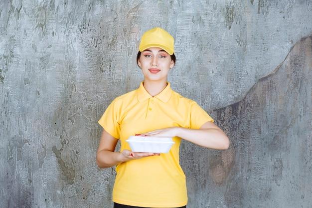 Weiblicher kurier in gelber uniform, der eine weiße box zum mitnehmen liefert.