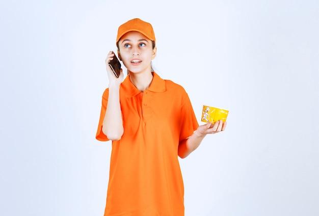 Weiblicher kurier in gelber uniform, der einen nudelbecher zum mitnehmen hält und bestellung vom smartphone entgegennimmt.