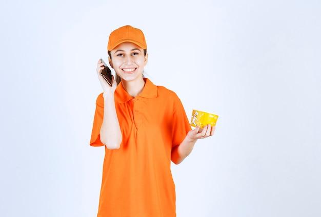 Weiblicher kurier in gelber uniform, der einen nudelbecher zum mitnehmen hält und bestellung vom smartphone entgegennimmt