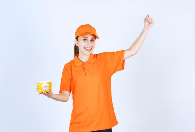Weiblicher kurier in gelber uniform, der einen nudelbecher zum mitnehmen hält und ihre faust zeigt.