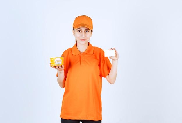 Weiblicher kurier in gelber uniform, der einen nudelbecher zum mitnehmen hält und ihre visitenkarte präsentiert.