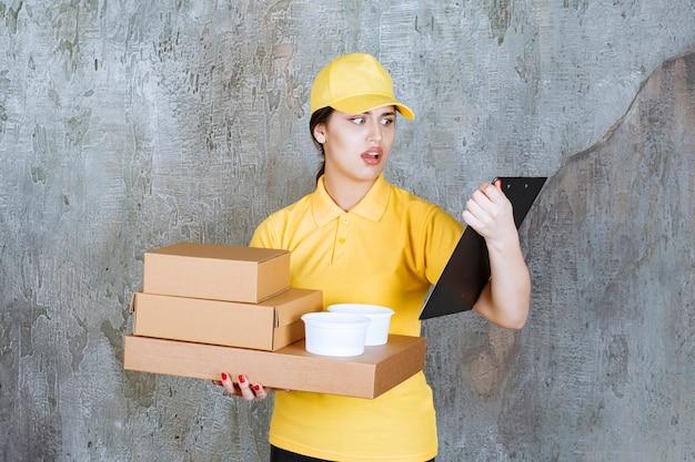 Weiblicher kurier in gelber uniform, der mehrere kartons und tassen zum mitnehmen liefert und die adresse auf der liste überprüft.