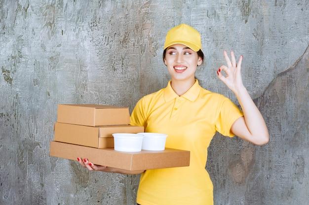 Weiblicher kurier in gelber uniform, der mehrere kartons und tassen zum mitnehmen liefert und ein positives handzeichen zeigt