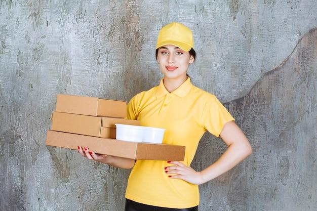 Weiblicher kurier in gelber uniform, der mehrere kartons und tassen zum mitnehmen liefert.