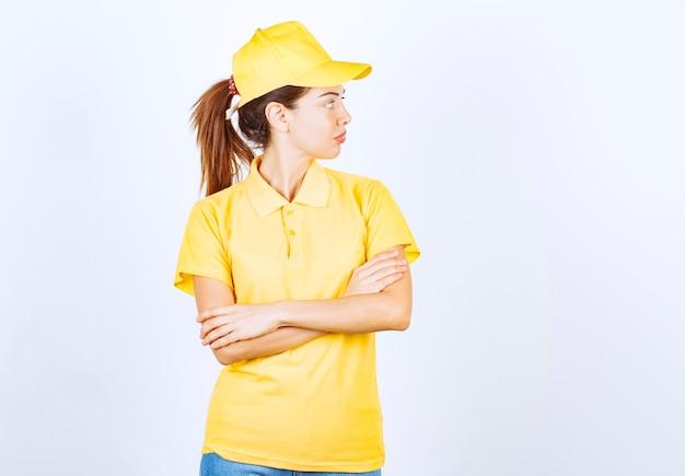 Weiblicher kurier in gelber uniform, die arme kreuzt und professionelle posen gibt.