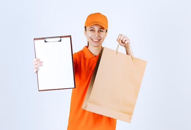 Weiblicher kurier in gelber uniform, die eine einkaufstasche liefert und die unterschriftenliste präsentiert.