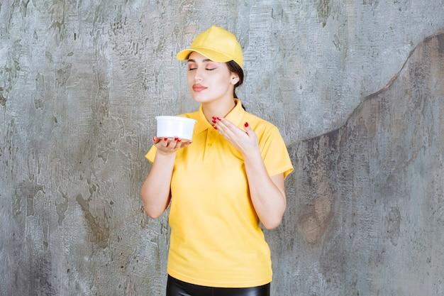Weiblicher kurier in gelber uniform, die eine tasse zum mitnehmen hält und das produkt riecht.