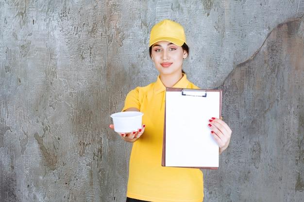 Weiblicher kurier in gelber uniform, die eine tasse zum mitnehmen hält und die taskliste zur unterschrift präsentiert.