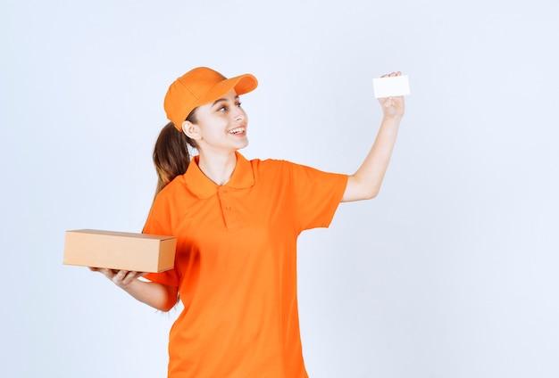 Weiblicher kurier in gelber uniform, die einen karton liefert und ihre visitenkarte präsentiert.