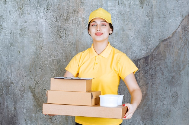 Weiblicher kurier in gelber uniform, die mehrere pappkartons und mitnehmerbecher liefert.