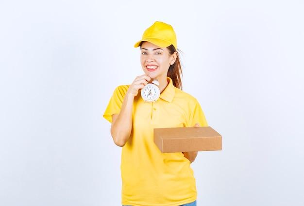 Weiblicher kurier in gelber uniform mit einem karton und einem wecker, was die pünktliche expresslieferung bedeutet.
