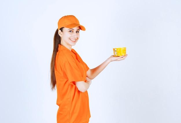Weiblicher kurier in gelber uniform mit einem nudelbecher zum mitnehmen.