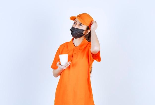 Weiblicher kurier in gelber uniform und schwarzer maske, der ein getränk zum mitnehmen hält und denkt