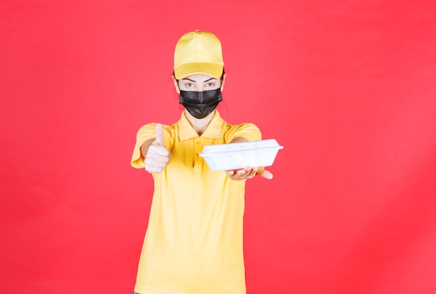 Weiblicher kurier in gelber uniform und schwarzer maske, der ein paket zum mitnehmen hält und ein positives handzeichen zeigt