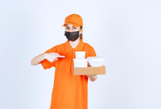 Weiblicher kurier in gelber uniform und schwarzer maske, der ein papppaket hält, speisen und getränke zum mitnehmen hält und auf sie zeigt.