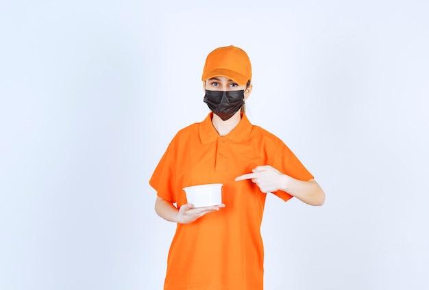 Weiblicher kurier in gelber uniform und schwarzer maske, der einen plastikbecher hält und auf etwas zeigt.
