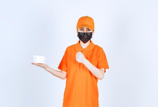 Weiblicher kurier in gelber uniform und schwarzer maske, der einen plastikbecher hält und ihre faust zeigt.
