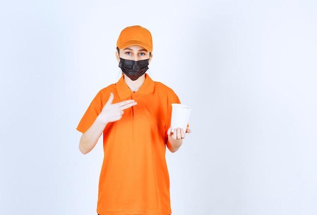 Weiblicher kurier in gelber uniform und schwarzer maske, der einen plastikbecher zum mitnehmen hält und darauf zeigt.